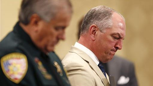 Louisiana Gov. John Bel Edwards, right, bows his head in prayer with Baton Rouge Sheriff Sid J. Gautreaux III at a prayer vigil for Alton Sterling, who was shot by Baton Rouge police in Baton Rouge, La., Thursday, July 7, 2016.