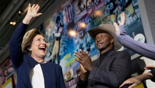 Democratic presidential candidate Hillary Clinton, left, accompanied by retired Pittsburgh Steelers Mel Blount, right, takes the stage at a rally at Heinz Field in Pittsburgh, Friday, Nov. 4, 2016.