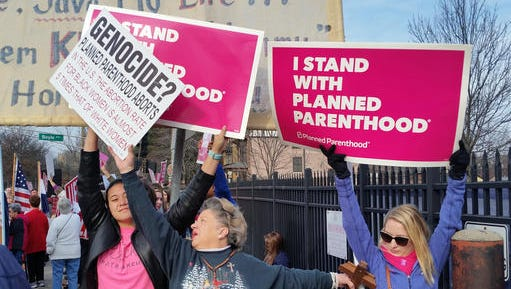 A Planned Parenthood supporter and opponent try to block each other's signs during a protest and counter-protest Saturday, Feb. 11, 2017 in St. Louis.   Rallies aimed at urging Congress and President Donald Trump to end federal funding for Planned Parenthood are scheduled across the country.