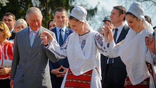 Britain's Prince Charles, left, joins a traditional folk dance in Bucharest, Romania, Thursday, March 30, 2017. Britain's Prince Charles toured the Village Museum during his visit to Romania, Italy and Austria, a trip seen as an effort to reassure European Union nations that Britain remains a close ally.