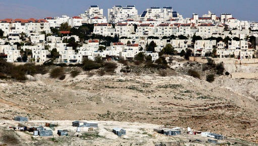 FILE -- In this Sunday, Jan. 22, 2017 file photo, the Israeli settlement of Maaleh Adumim looms over Arab Bedouin shacks in the West Bank. Prime Minister Benjamin Netanyahu has ordered a slowdown of construction in territory Palestinians want for a state in a gesture to President Donald Trump at the same cabinet meeting where he approved the first new settlement in two decades the heart of the West Bank. Netanyahu's government is dominated by pro-settler hard-liners who oppose Palestinian statehood on either security or religious grounds.