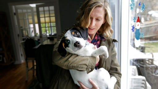 In this Wednesday, March 29, 2017 photo Kate Fredette, of Waltham, Mass., holds the family dog Roscoe at their home in Waltham. The Fredette family found the dog through the online platform How I Met My Dog, that matches humans with dogs based on what really matters: personality, lifestyle and behavior.