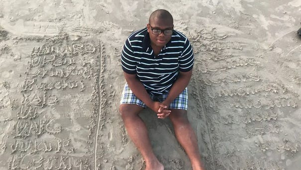 Micheal Brown, 17, sits in the sand next to the...