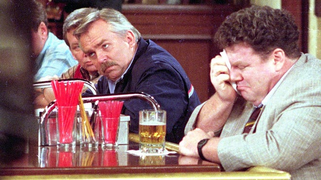 """George Wendt, right, who portrays Norm Peterson sheds a tear on the set of the popular NBC series, """"Cheers,"""" as John Ratzenberger, portraying Cliff Calvin, looks away during a scene while taping the final episode in Los Angeles, Calif., on April 1, 1993."""