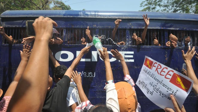 Burma student protesters and activists gesture from a departing police truck following a court hearing in Letpadan on April 7, 2015.