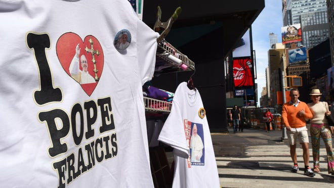 T-shirt vendors sell Pope Francis shirts in Times Square in New York on Sept. 21, 2015, as the city prepares for his visit.