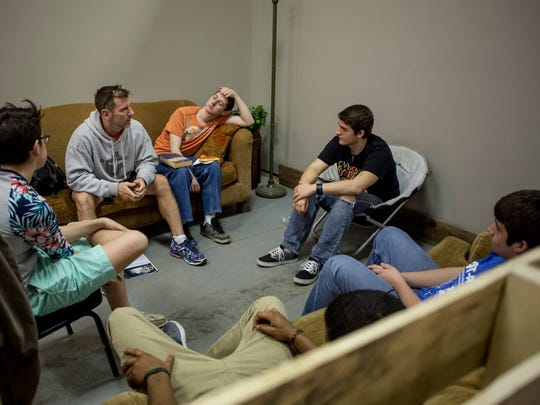 Gordon Farnsworth leads a group discussion with students in a lounge area May 4 at the Impulse Student Ministries youth center.