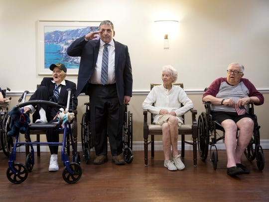 Carl Carrano, 63, salutes during the national anthem at the ceremony to honor veterans on Wednesday, June 14, 2017, at Memory Care of Naples. Carrano served for 25 years in the Army, and seated around him are fellow veterans who are residents at Memory Care of Naples.