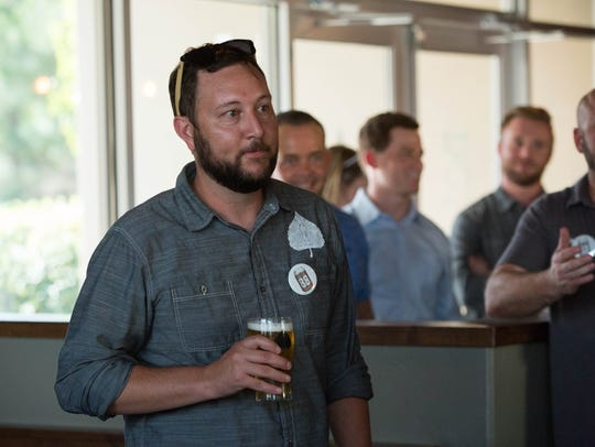Gabe Jensen, one of the owners of Bosque Brewing Co., stands in the Las Cruces Taproom holding a Pistol Pete's 1888 Ale during the announcement celebration Thursday Aug. 17, 2017.