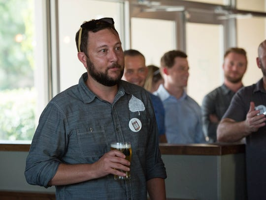 Gabe Jensen, one of the owners of Bosque Brewing Co. stands in the Las Cruces Taproom  holding a Pistol Pete's 1888 Ale, during the announcement celebration Thursday Aug. 17, 2017.