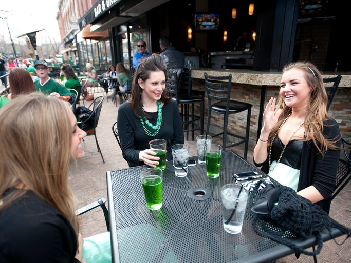 From left, Jennifer Hambleton, Kelsie Coombes and Samantha DiPilato enjoy green beer at the Rec Room on St. Patrick's Day in Old Town Square in Fort Collins Monday, March 17, 2014.