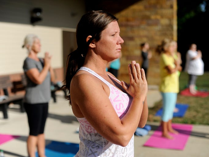 Visitors participate in a yoga class held at Hopewell Culture National Historical Park on Saturday. The free class is part of the Healthy Parks, Healthy People Initiative and is led by local yoga instructor Terry Dunlap, owner of Living Balance Yoga Therapy Studio.