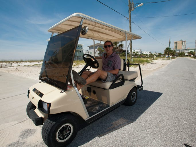 Pensacola Beach resident and business owner Nate Holler travels around Santa Rosa Island using a golf cart. Pensacola Beach has been trying to become a Golf Cart Community, one that allows abundant use of golf carts on its roadways. It sought an ordinance from Escambia County to OK the use of the carts on the county owned main roads of Via de Luna, Fort Pickens Road and Pensacola Beach Boulevard. But county commissioners took no action last week, only saying beach visitors and residents must adhere to state laws, which allow golf carts on roads with posted speed limits of 35 mph, only if they are street legal with head and tail lights, wind shield, mirrors and are insured and have car tags. A licensed driver can only operate them.