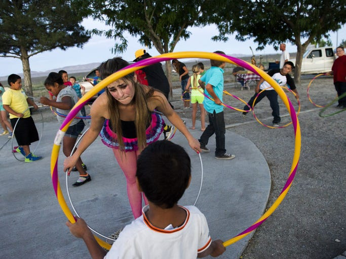 Destynee Howell helps children hula hoop after performing at the Lovelock Compression, Art & Fire Festival on Friday, June 20, 2014, in Amherst Park in Lovelock, Nev.
