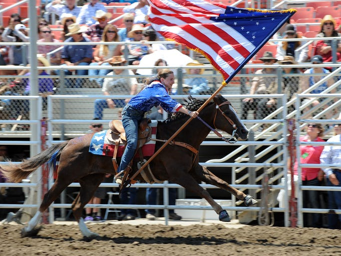 A historical American flag enters the arena during the ceremonial Pageant of Flags on Sunday's Day of Champions at the 2014 California Rodeo Salinas.