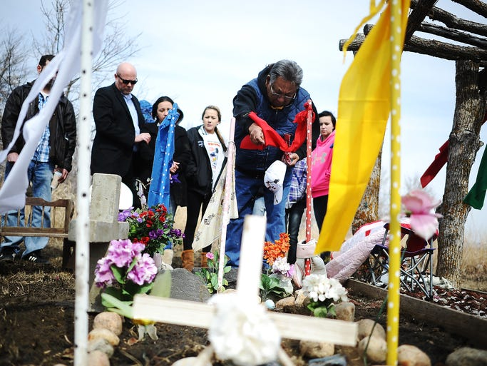 Clifford Canku sprinkles tobacco over the newly placed headstone of his granddaughter, Aleeyah Cook, during a traditional Dakota memorial service for Cook on Wednesday, March 26, 2014, at the Cook family home near Sisseton, S.D. Aleeyah Cook, who was 2-years-old at the time of her death, was killed by her father, Mario Contreras, in January of 2012. Robert Shepherd, Sisseton Wahpeton Oyate tribal chairman, wrote a letter supporting Contreras on tribal letterhead, which alienated Aleeyah's family members, causing a split in Sisseton Wahpeton Oyate tribal members. (Joe Ahlquist / Argus Leader)