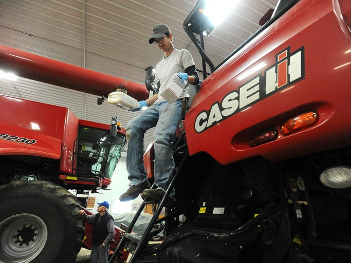 Blake Krumbach works on a combine in preparation for harvest season on May 13, 2014.