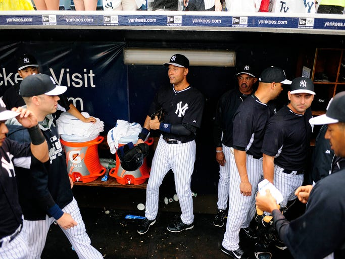 New York Yankees shortstop Derek Jeter picks up his equipment during his last spring training experience, one that was rained out in Tampa, Fla.