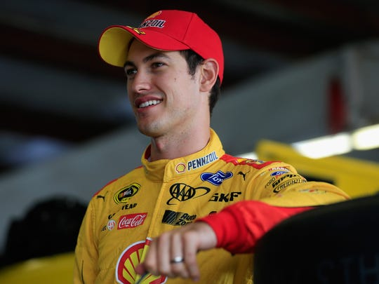 Joey Logano stands in the garage area during practice