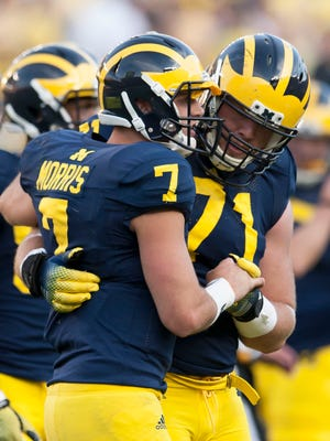 Shane Morris is assisted by Ben Braden after suffering a concussion against Minnesota.