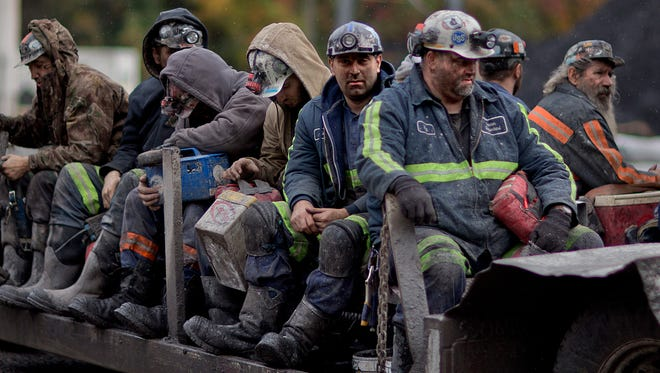 Coal miners return on a buggy after working a shift underground at the Perkins Branch Coal Mine in Cumberland, Ky.
