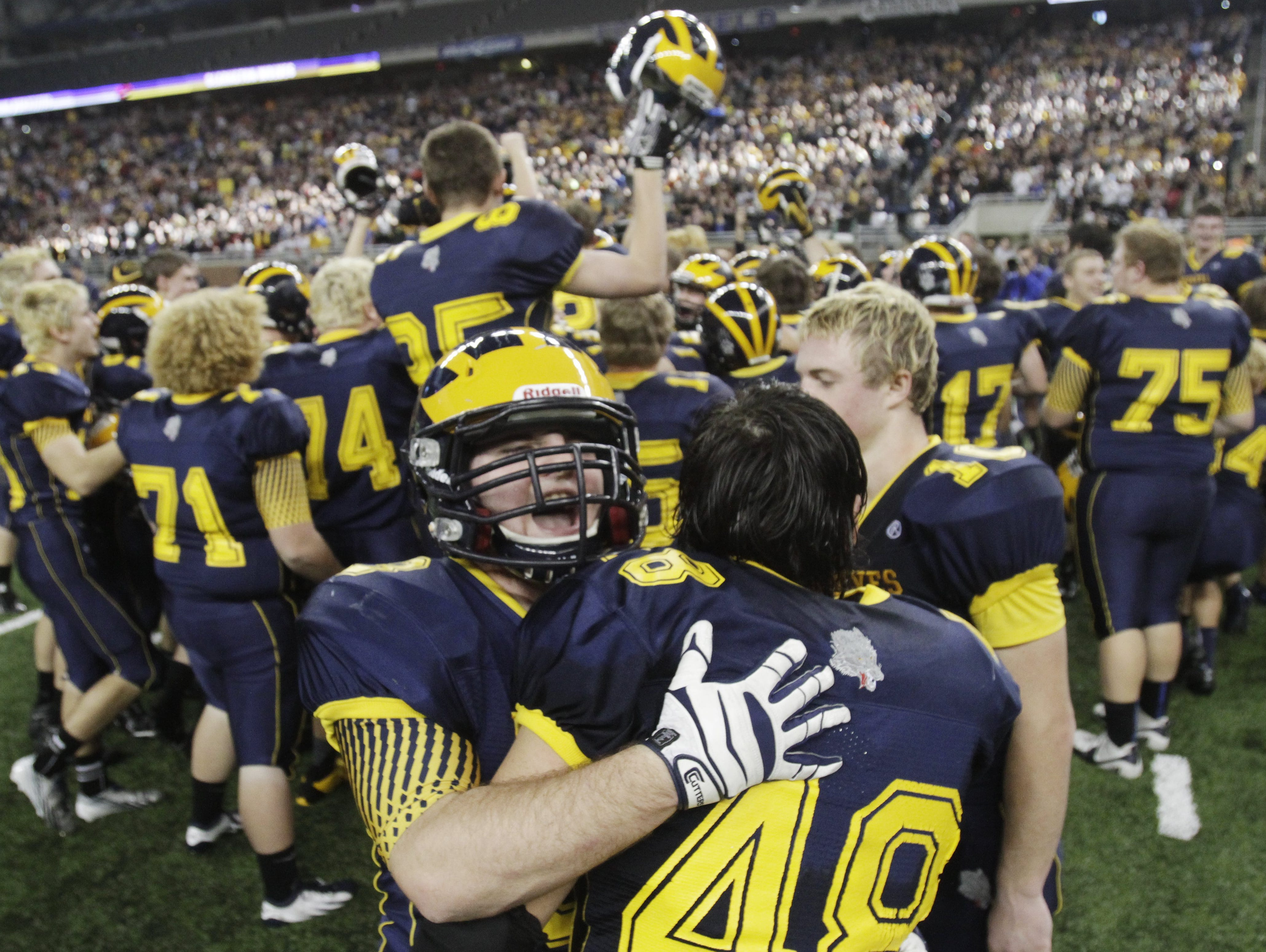 Clarkston players celebrate their Division 1 title win against Novi Detroit Catholic Central on Nov. 30, 2013, at Ford Field.