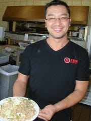 Tony Quach brings out a plate of chicken fried rice