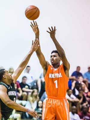 Javon Bess (1) shoots over Drew Valentine during their Moneyball Pro-Am game Tuesday July 1, 2014 in Lansing.