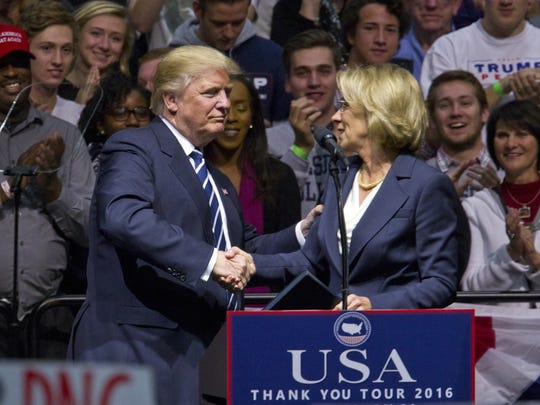 """President-elect Donald J. Trump greets Betsy DeVos, his choice for education secretary, during his """"USA Thank You Tour"""" at the DeltaPlex in Walker, Mich., Friday, Dec. 9, 2016."""