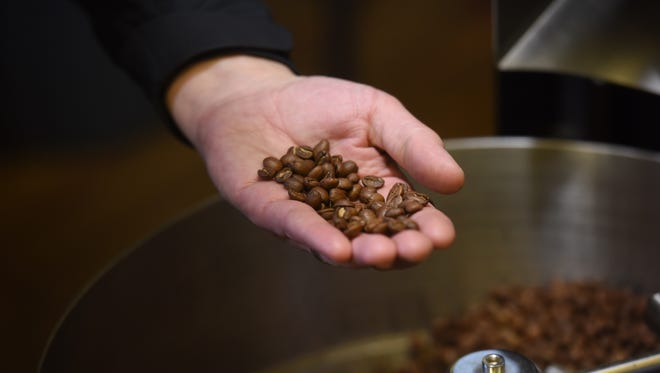 Corey Gerlach holds roasted coffee beans at the Breaks Coffee Roasting Co. on Thursday in Sioux Falls.