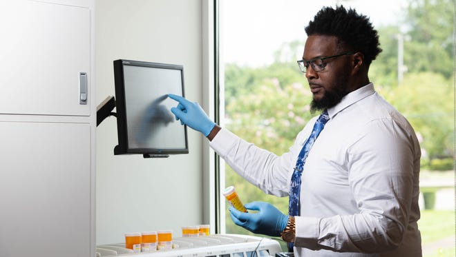 Mail-Meds pharmacy tech Wendell Williams operating the ScriptPro Robotic Dispensing System which can process up to 150 prescriptions per hour.