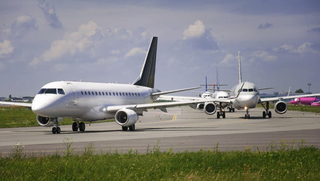 Air planes wait on an airport runway.