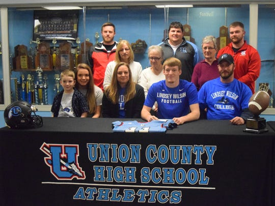 Logan Thomas surrounded by his family and coaches as he signed to play collegiate football at Lindsey Wilson College.