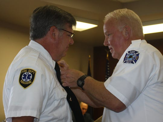 Fort Thomas Fire Department Chief Mark Bailey, right, pins a captain's rank onto Jeff Parker to signify the promotion at the June 16 Fort Thomas City Council meeting.