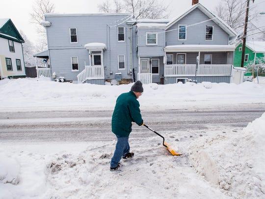 Joe Greene clears his driveway after a snowfall in
