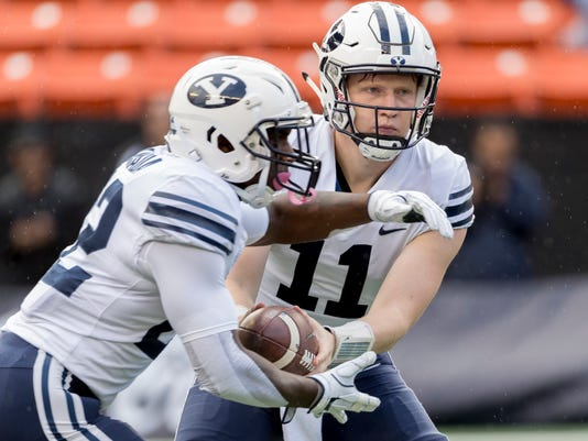 BYU quarterback Joe Critchlow (11) hands off the football to running back Squally Canada (22) in the first quarter of an NCAA college football game, Saturday, Nov. 25, 2017, in Honolulu. (AP Photo/Eugene Tanner)