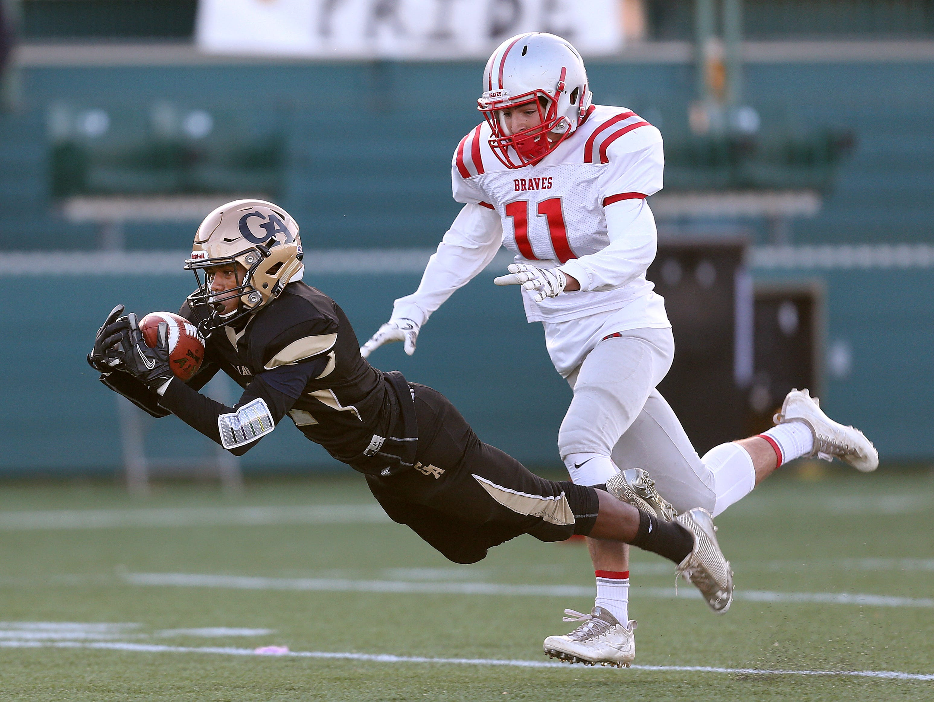 Athena's Kenny Speed (4) makes a diving catch against Canandaigua's Carson Greene (11) to help set up a touchdown.