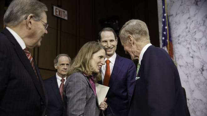 Sylvia Mathews Burwell is surrounded by members of the Senate Finance Committee at the start of her confirmation hearing May 14.