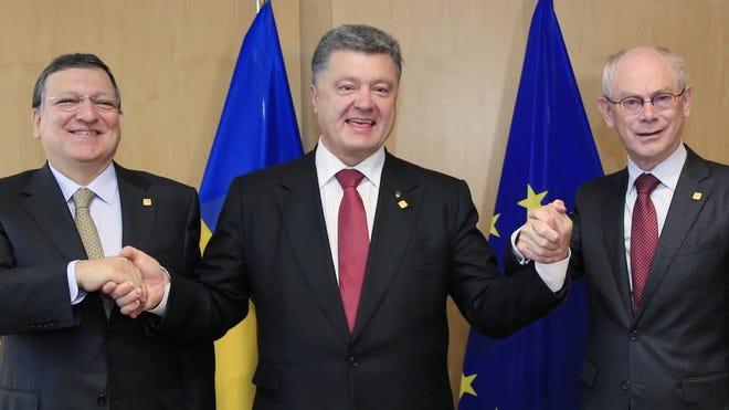 Ukrainian President Petro Poroshenko, center, with European Commission President Jose Manuel Barroso, left, and European Council President Herman Van Rompuy in Brussels on June 27.