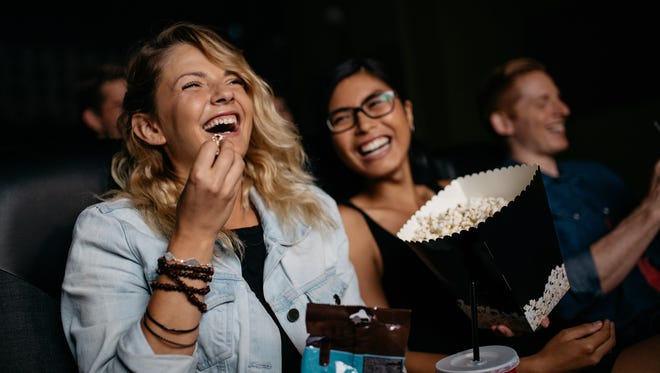 Young woman with friends watching movie in cinema and laughing. Group of people in theater with popcorns and drinks.