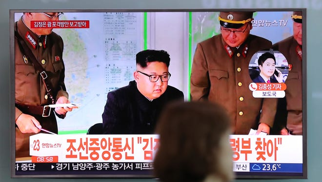 A woman walks by a TV screen showing a local news program reporting about North Korean military's plans to launch missiles into waters near Guam, with an image of North Korean leader Kim Jong Un, at Seoul Train Station in Seoul, South Korea, Tuesday, Aug. 15, 2017.