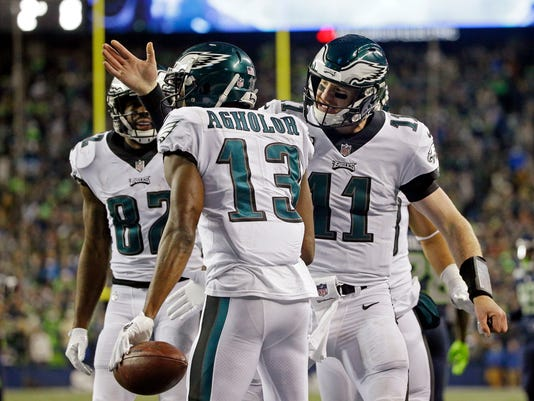Philadelphia Eagles quarterback Carson Wentz (11) congratulates Nelson Agholor (13) on his touchdown reception against the Seattle Seahawks during the second half of an NFL football game, Sunday, Dec. 3, 2017, in Seattle. (AP Photo/Ted S. Warren)