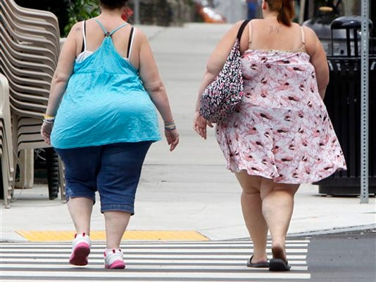 Two women cross the street in Barre, Vt. In its biggest policy change on weight and health to date, the American Medical Association has recognized obesity as a disease. (Associated Press -- Toby Talbot)