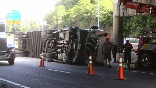 Workers prepare to right a tractor-trailer that overturned on I-287 westbound under the Route 1 bridge in on the Port Chester-Rye line Tuesday, May 31, 2016. Traffic backed up into Connecticut with only one lane open at the site of the accident.