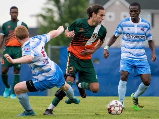 The Bucks' Marco Charalambous (middle) splits two Lansing
