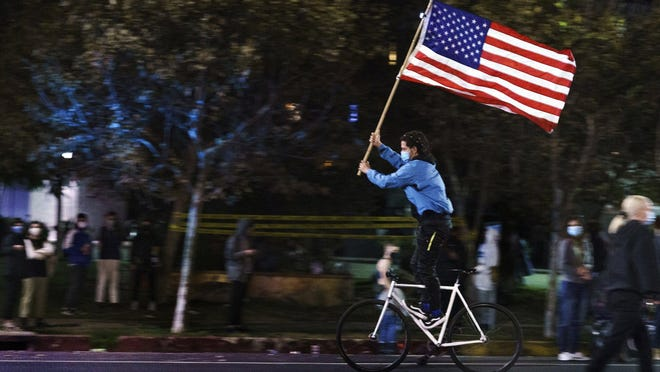 A supporter of President-elect Joe Biden and Vice President-elect Kamala Harris rides standing on his bicycle Saturday as he parades with the flag on Sunset Boulevard in Los Angeles.