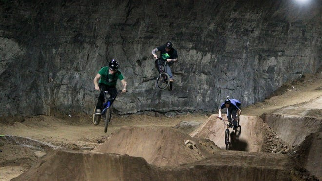 Derek Fetko, left, Joe Prisel and Jeff Perkins demonstrate dirt jumping at a new course being built inside the Mega Caverns.