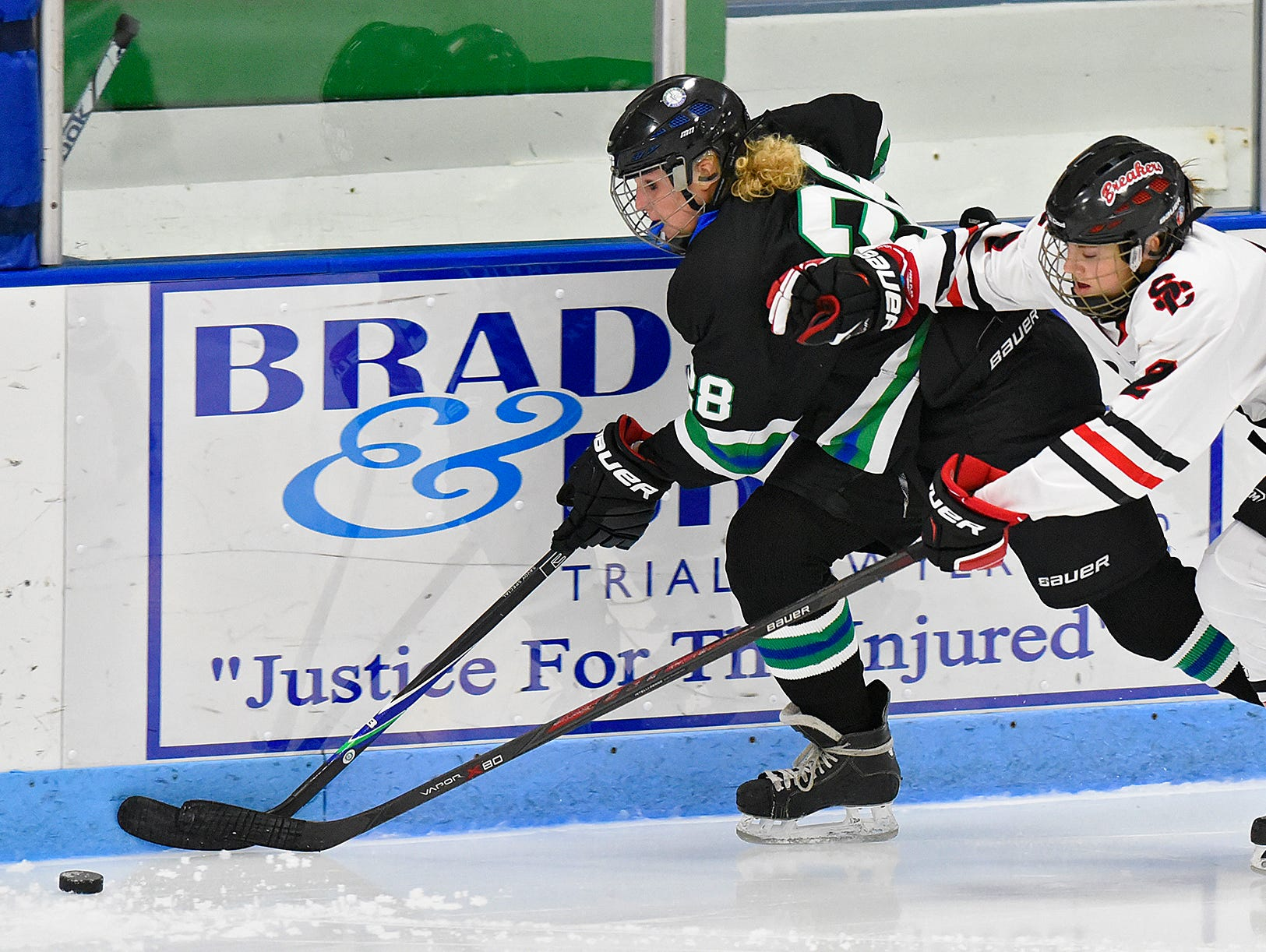 Allie Hemmesch of the Storm 'N Sabres struggles for control of the puck with Sophia McCann of the Icebreakers during the first period of Thursday's game at the MAC in St. Cloud.