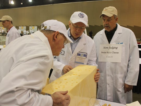 From left, judges Doug Anker and Greg Anderson, and volunteer Steve Stettler inspect a swiss cheese during the 2015 United States Championship Cheese Contest on Tuesday, March 17, 2015 in Milwaukee. The contest is the biggest ever, with a record 1,885 entries from 28 states.