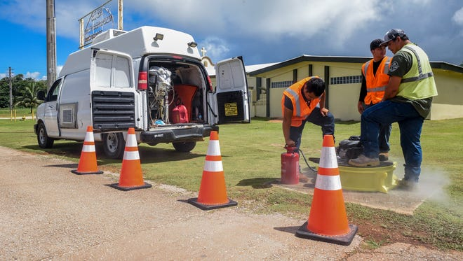 Guam Waterworks Authority employees, from left, Dominick San Nicolas, Shayne Terlaje and Craig Paulino, use a smoke machine to inject smoke into a manhole near the Santa Bernadita Chapel in Machanaonao, Yigo on Friday, Oct. 27, 2017. The tests were conducted to check the integrity and safety of the underground sewer by locating breaks and defects in the system, said Paulino.